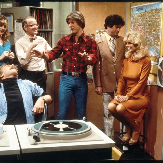 The cast of the television comedy 'WKRP in Cincinnati' share a laugh in the studio in a still from an unidentified episode, Los Angeles, Calfornia, 1980. Pictured are from left, American actors Tim Reid (as Venus Flytrap), Jan Smithers (as Bailey Quarters) (rear, in turquoise shirt), Howard Hesseman (as 'Dr. Johnny Fever' Caravella), Richard Sanders (as Les Nessman), Gary Sandy (as Andy Travis), Frank Bonner (as Herb Tarlek), and Loni Anderson (as Jennifer Elizabeth Marlowe).