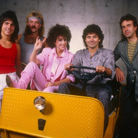 "LOS ANGELES, CA - 1988: Members of the rock group Starship, including Grace Slick and Mickey Thomas (in cart), pose together during a 1988 Los Angeles, California, photo portrait session. Starship, a bastardized version of Jefferson Starship, rode a wave of hits including ""We Built This City"" and ""Nothing's Gonna Stop Us Now."" (Photo by George Rose/Getty Images)"